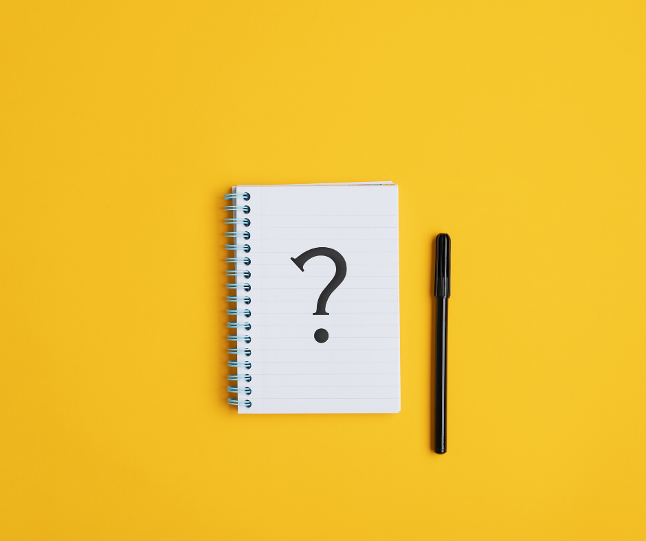 notebook with a large question mark and black pen on a yellow background