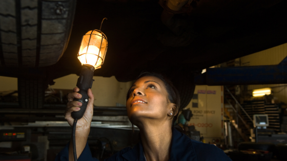 woman technician inspecting the underside of a car