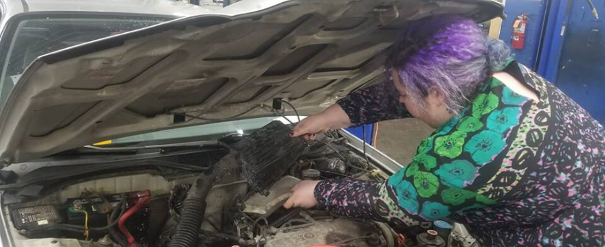 Chaya changing an air filter on a car