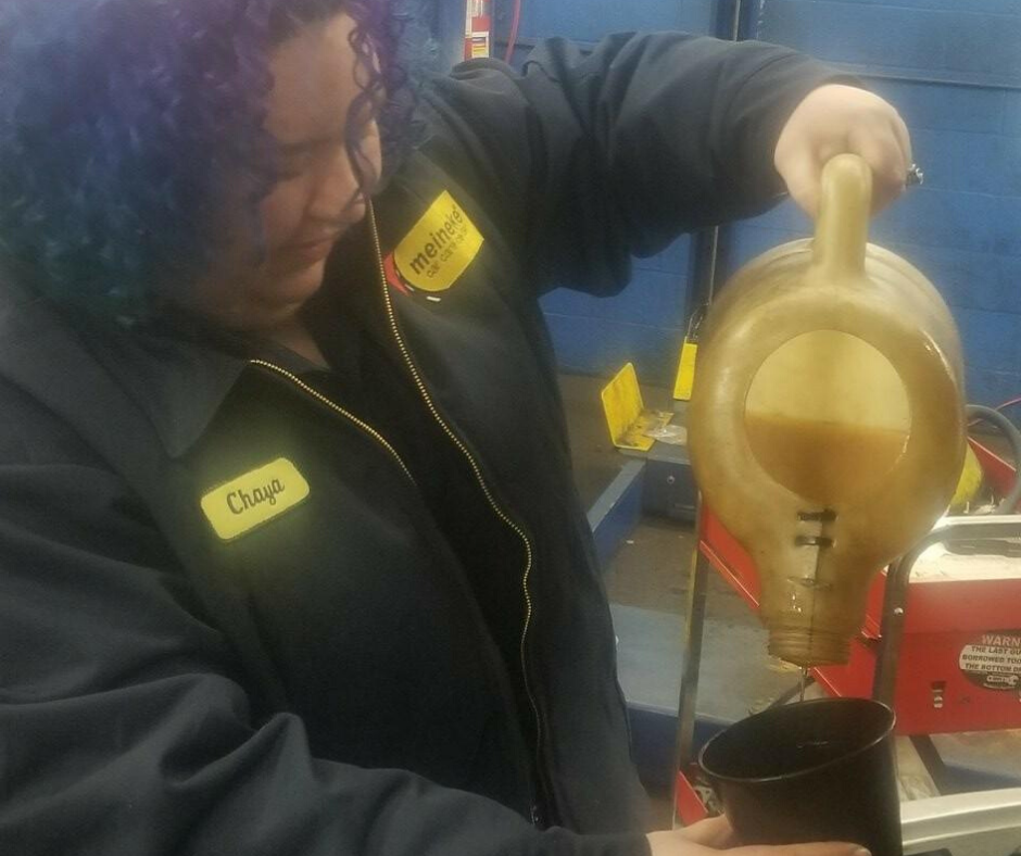 Chaya pouring engine oil into a funnel