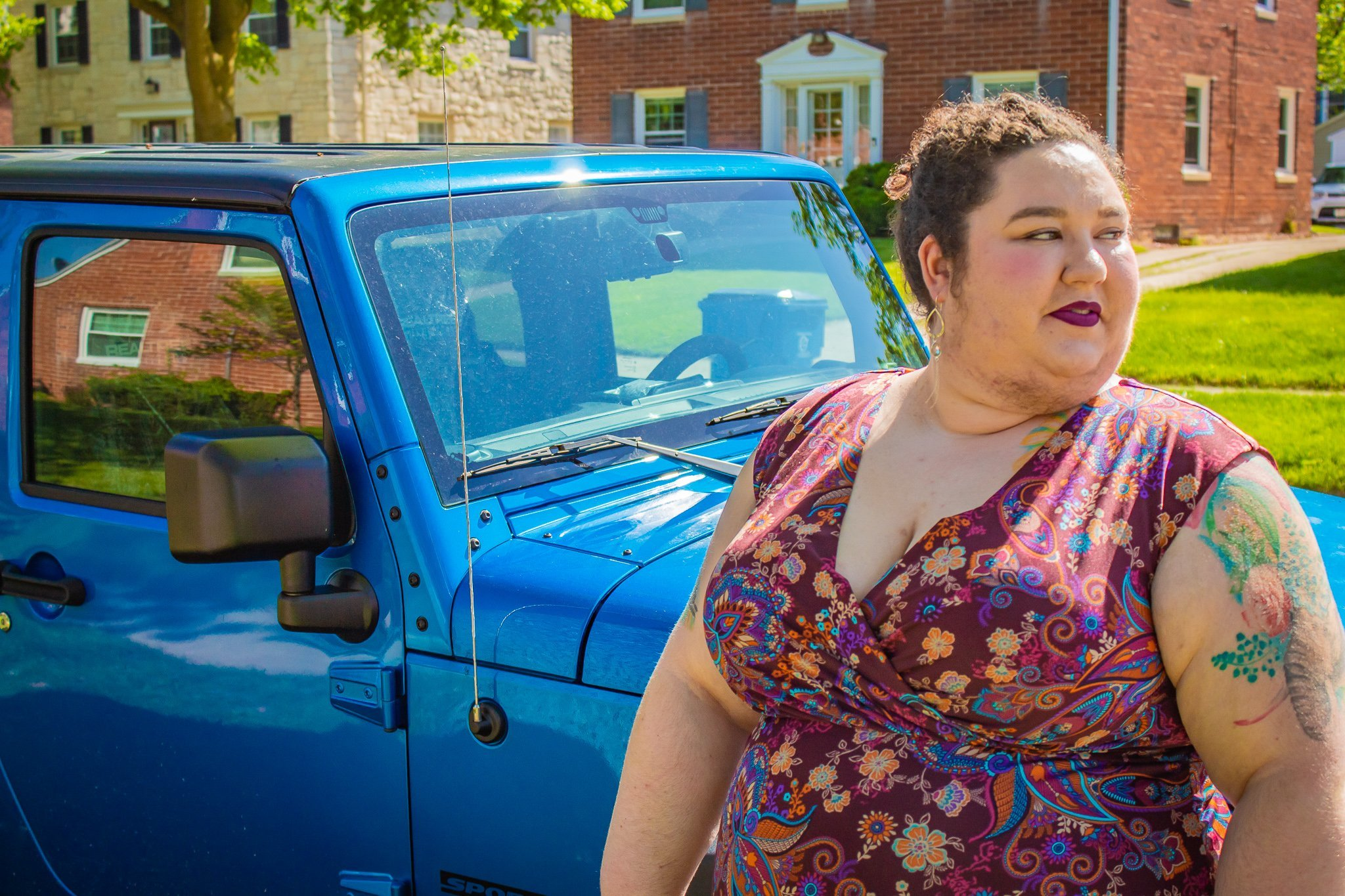 Chaya with her hair up, leaning against a blue jeep