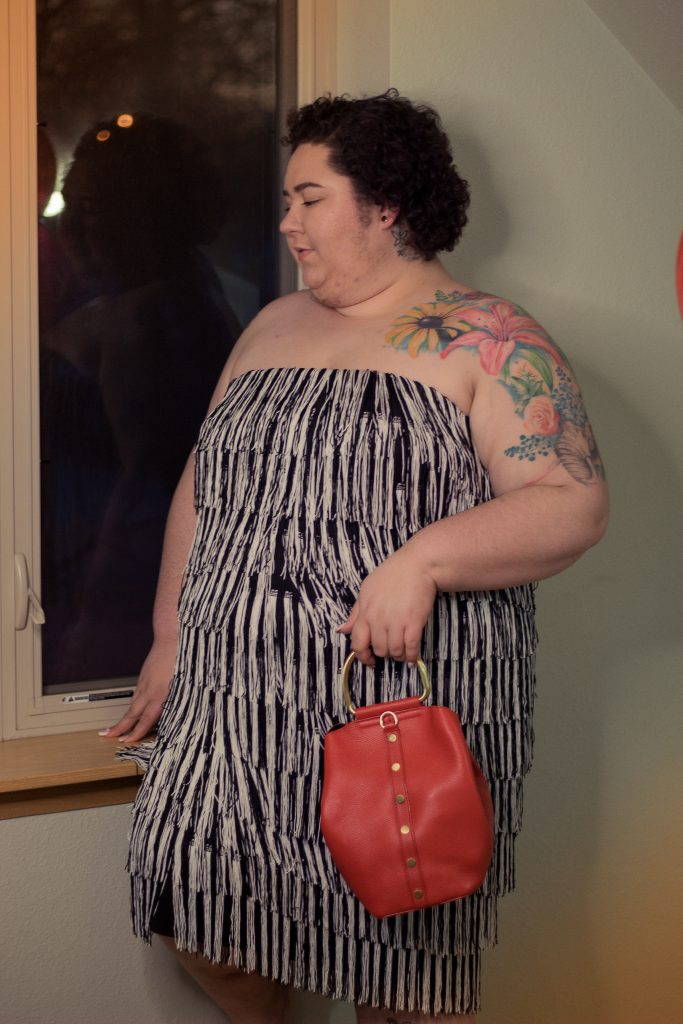 Plus size woman in a black and white fringe dress with a red purse.