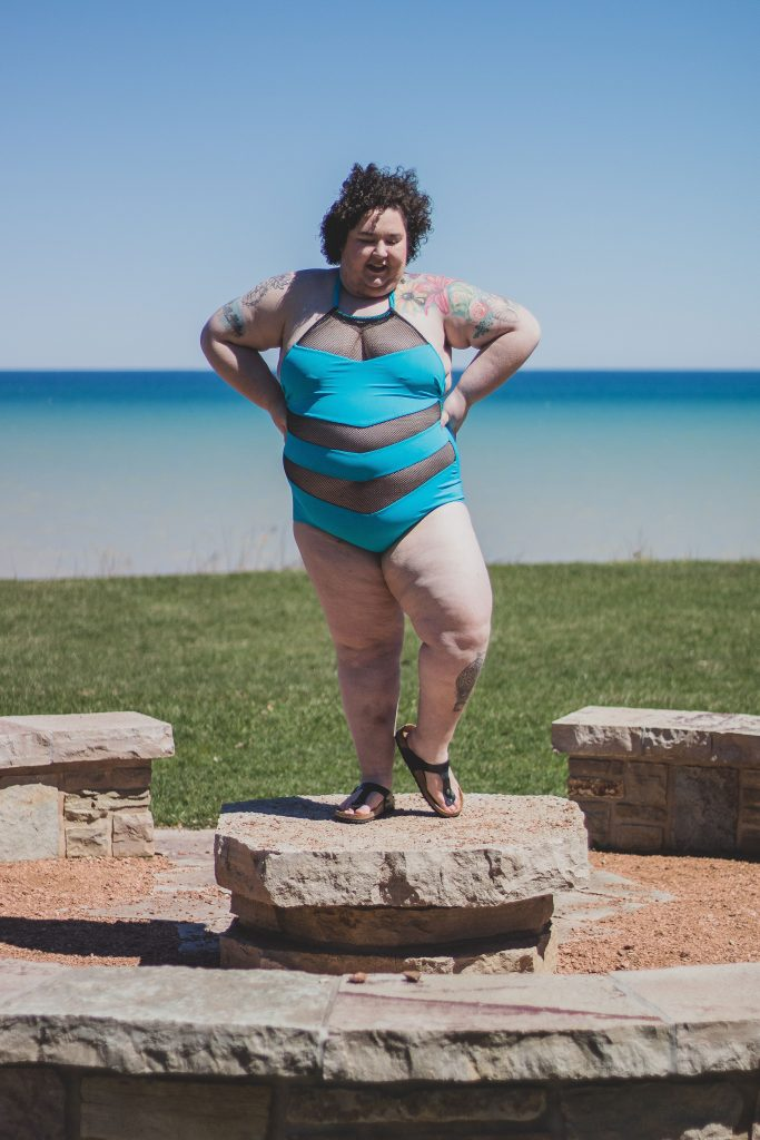 Plus size woman wearing a one peice bikini standing on a rock in from of the lake