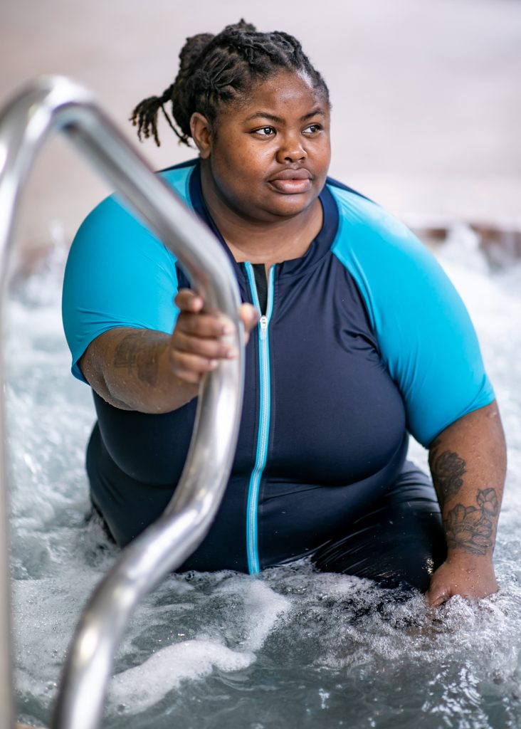 Plus size black woman wearing a swimsuit with short sleeves and knee length