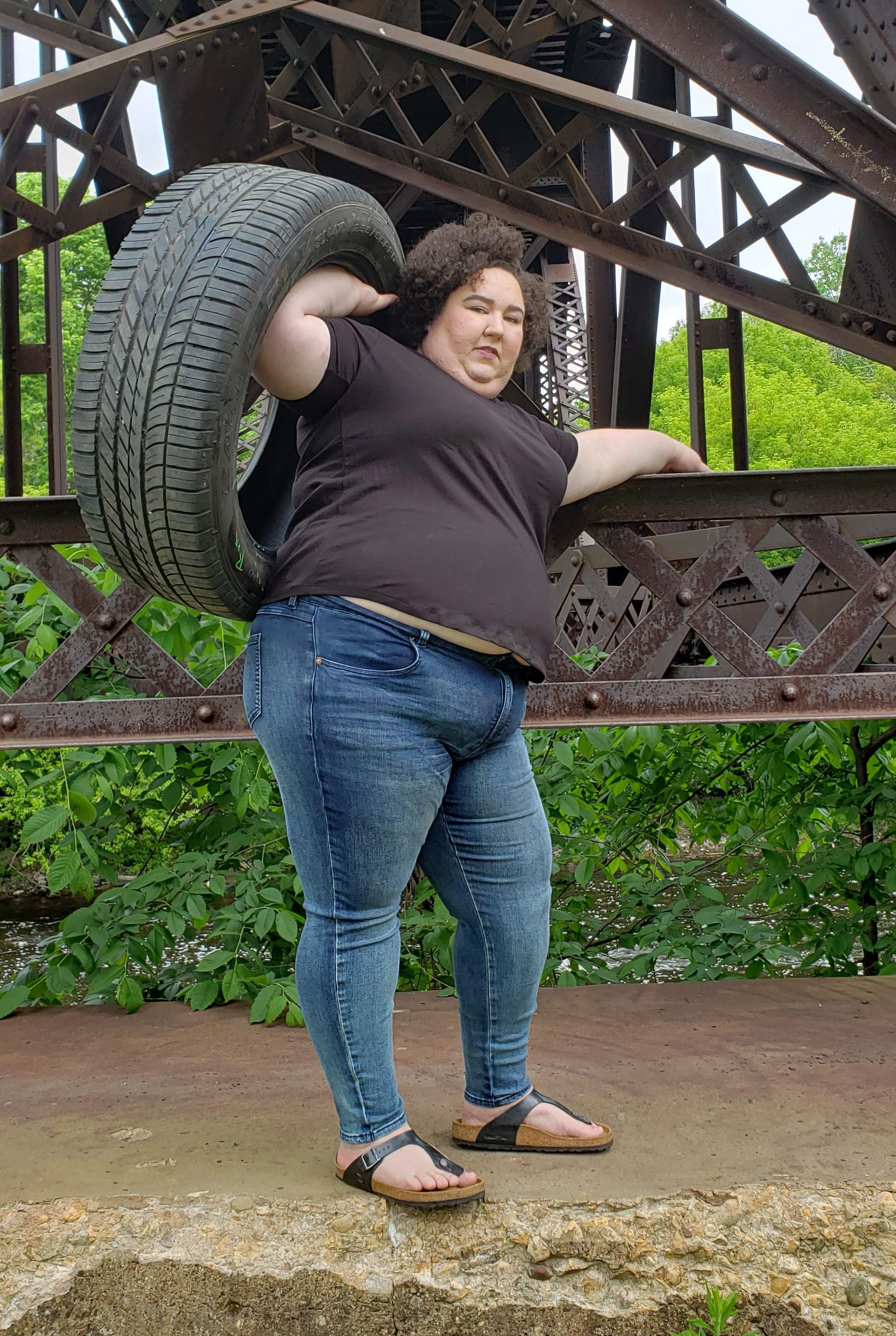 Chaya Milchtein standing on concrete ledge on a railroad area holding a truck tire in one hand and holding the metal ledge with the other wearing blue jeans and a black t shirt.