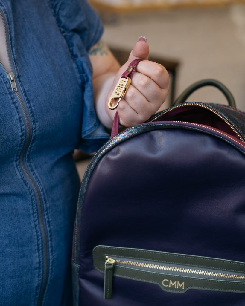 hand holding a keys clip coming out of a leather backpack