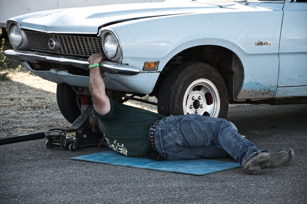 man laying on the ground under an old car trying to fix it.