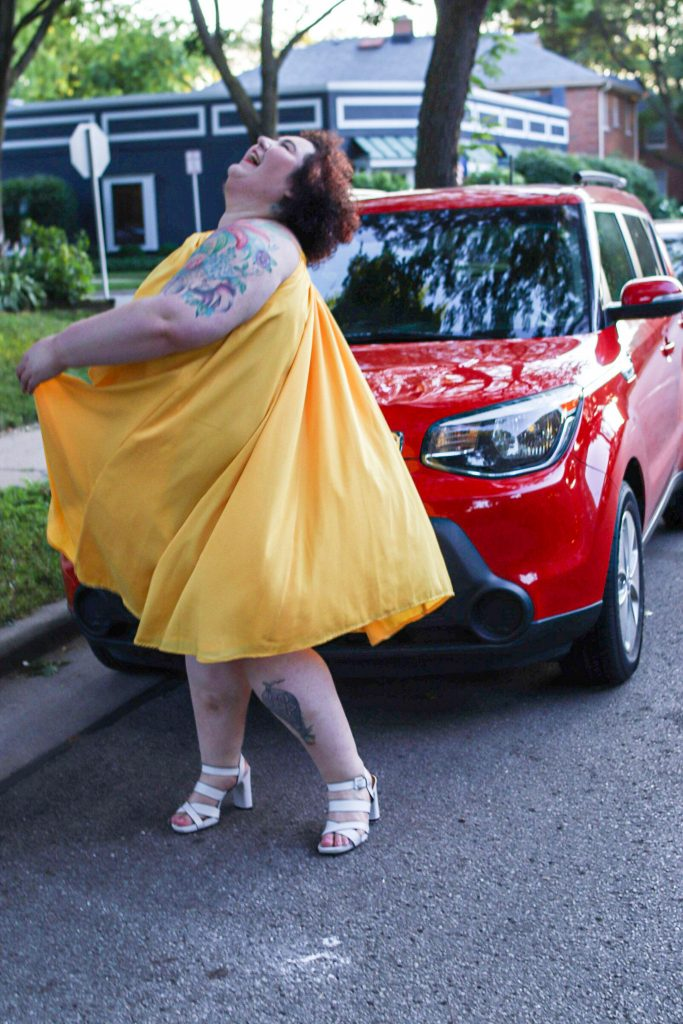 Chaya Milchtein standing in front of red kia wearing a yellow dress.