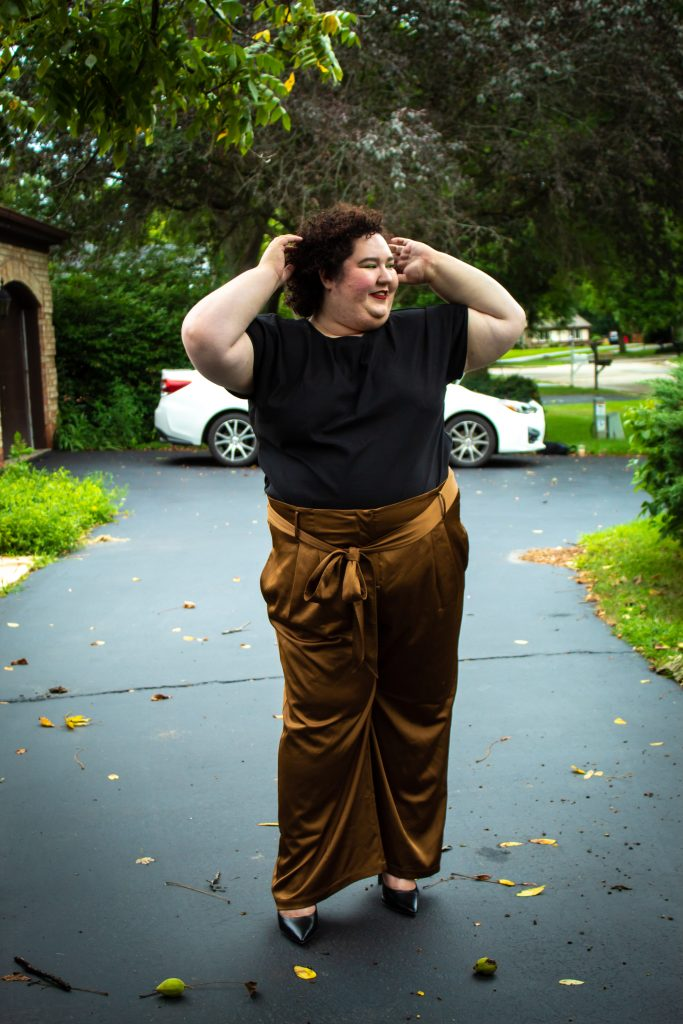 plus size woman wearing bronze pants and a black shirt