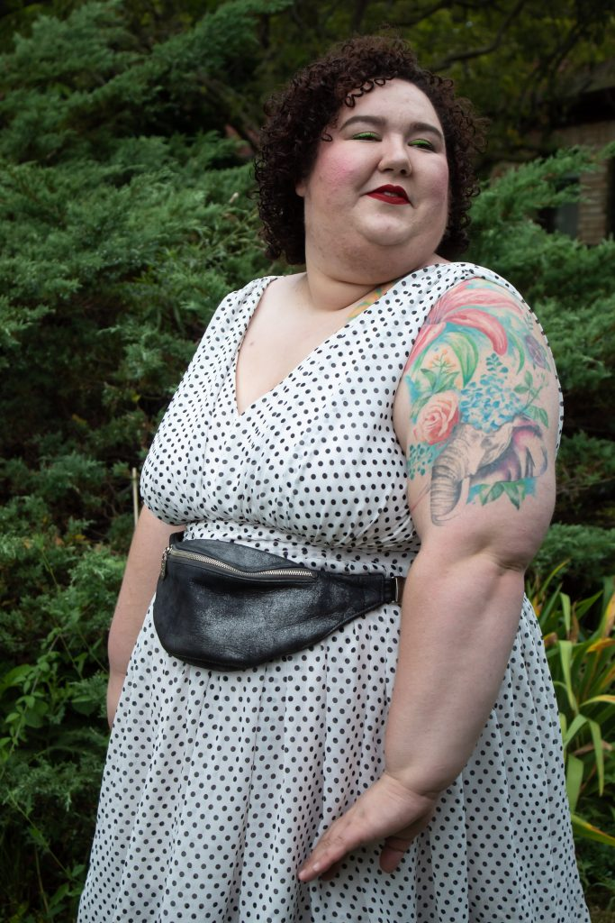 Chaya Milchtein a plus size woman wearing a polkadotted white dress with a black fanny pack.