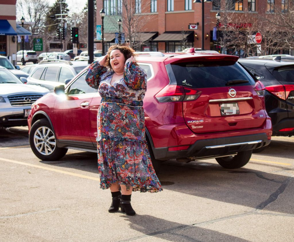 Plus size woman in a long flowy anthropologie dress standing in front of a red car in a parking lot.