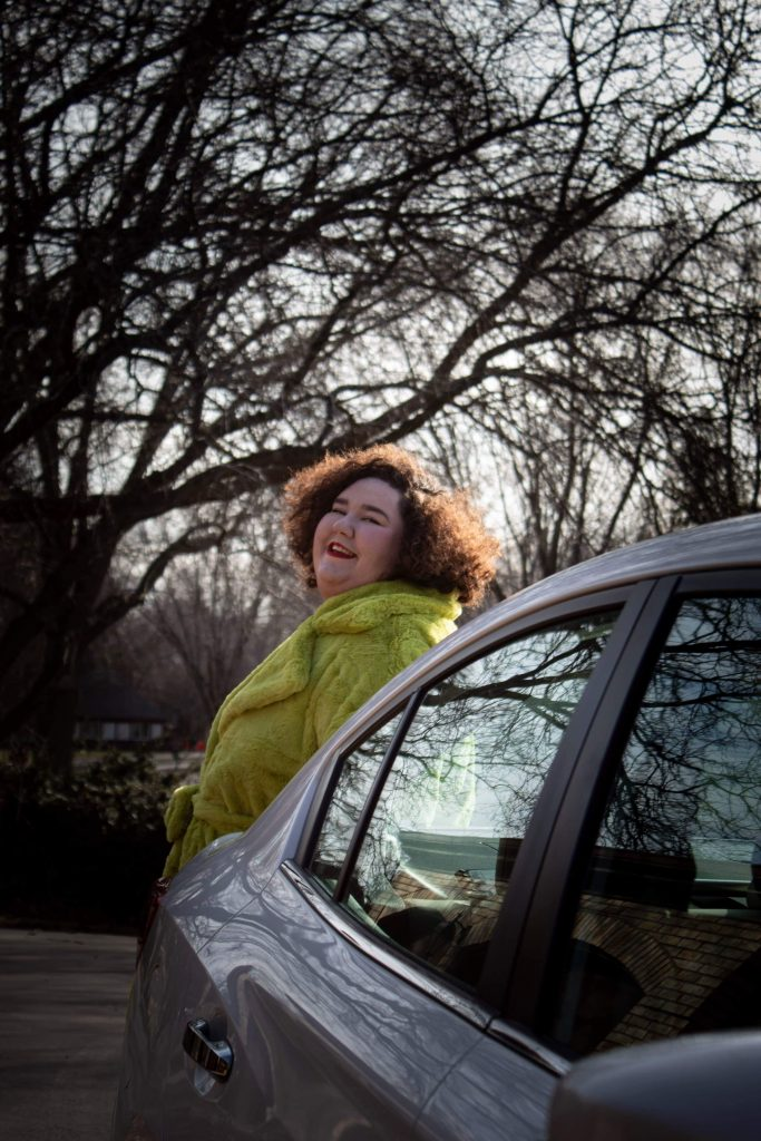 Plus size woman wearing an oversode green coat standing behind a white Subaru Impreza
