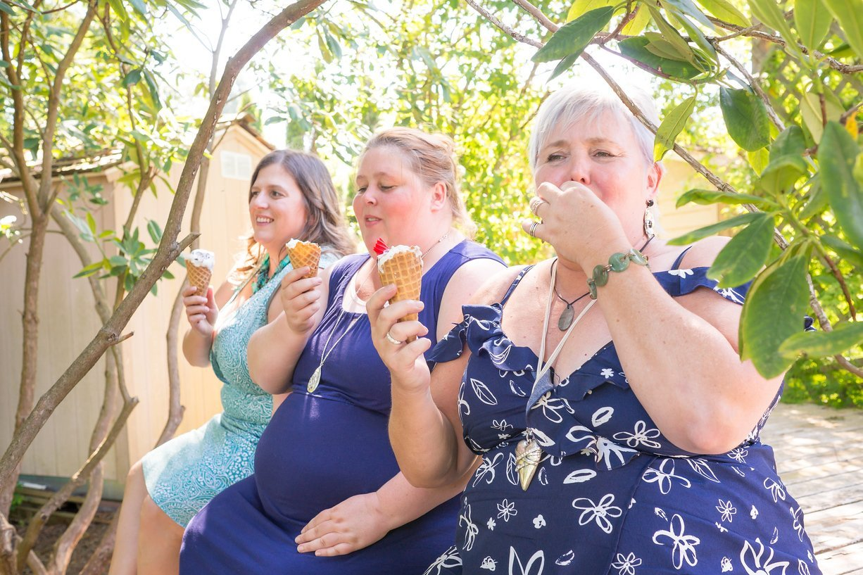 Three women sit on the edge of a wooden deck in the back yard of a house and enjoy ice cream cones for dessert in the shade of a garden with trees and bushes on a warm, sunny spring day. All of these women are in active recovery from eating disorders.rr- One woman is over 50 and has short silver or gray hair and tanned skin. She is wearing a dark blue off the shoulder dress with a white floral pattern.rr- One woman is in her 30s and has shoulder-length brown hair and pale skin. She's wearing a blue dress with a deep V-neck and a matching blue beaded necklace.rr- One woman is in her 30s and has shoulder-length dark blonde hair pulled up into a bun. She's wearing a dark blue dress and silver necklace.