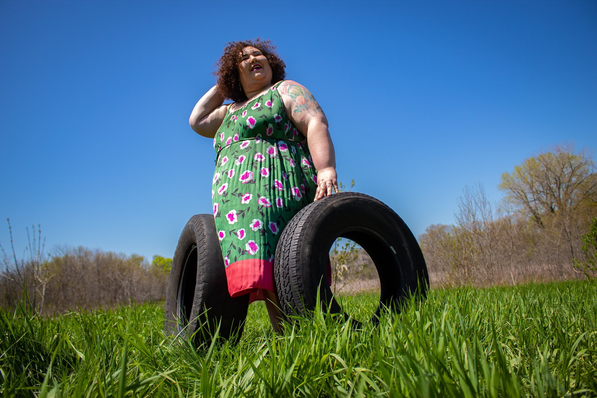 Chaya standing up with two tires leaning against her