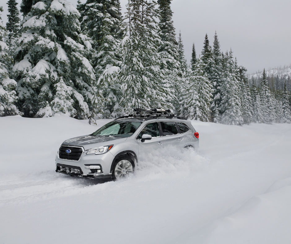 Subaru Ascent SUV driving down a snowy road with a bike rack on top