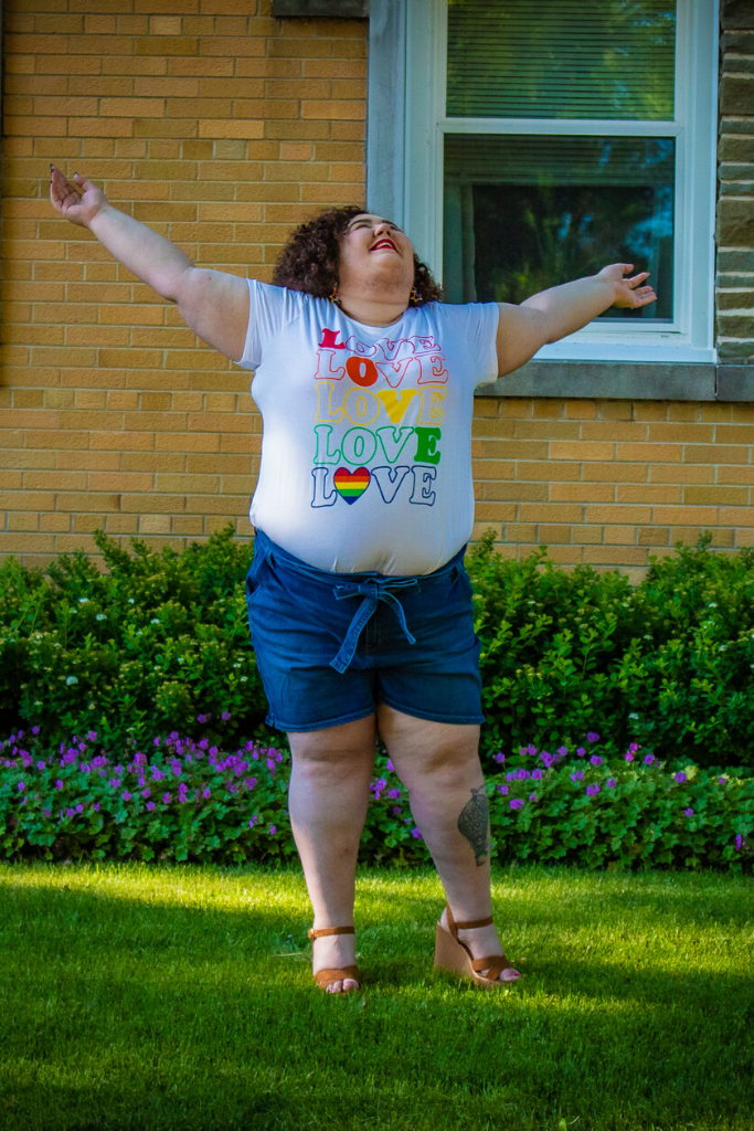 Chaya wearing Lane Bryant plus size shorts and a plus size pride tshirt