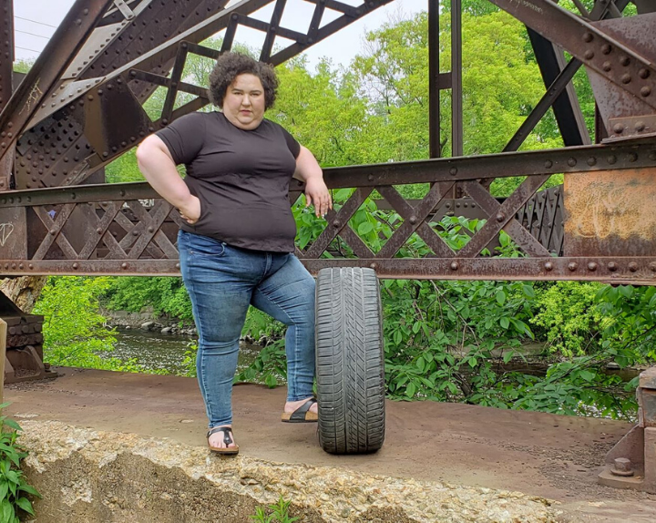 Chaya standing on a tire wearing Universal Standard jeans and tshirt