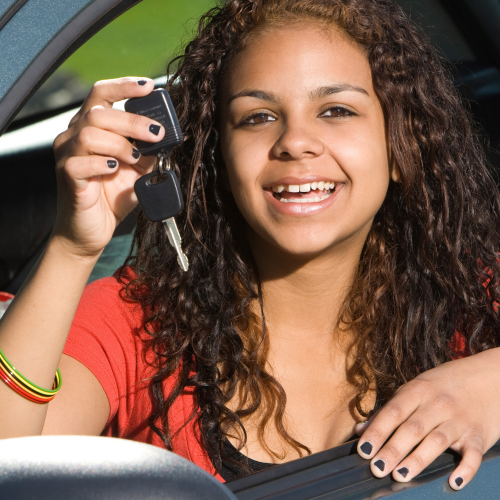 Young Black woman sitting inside her car holding up her keys like she just bought the car