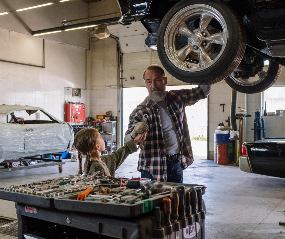 Mechanic showing a young girl how to fix a car