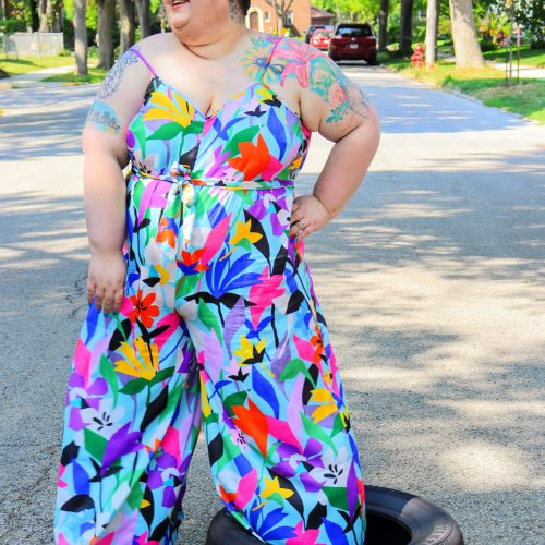 Chaya Milchtein standing in a tire, wearing an Eloquii plus size jumpsuit