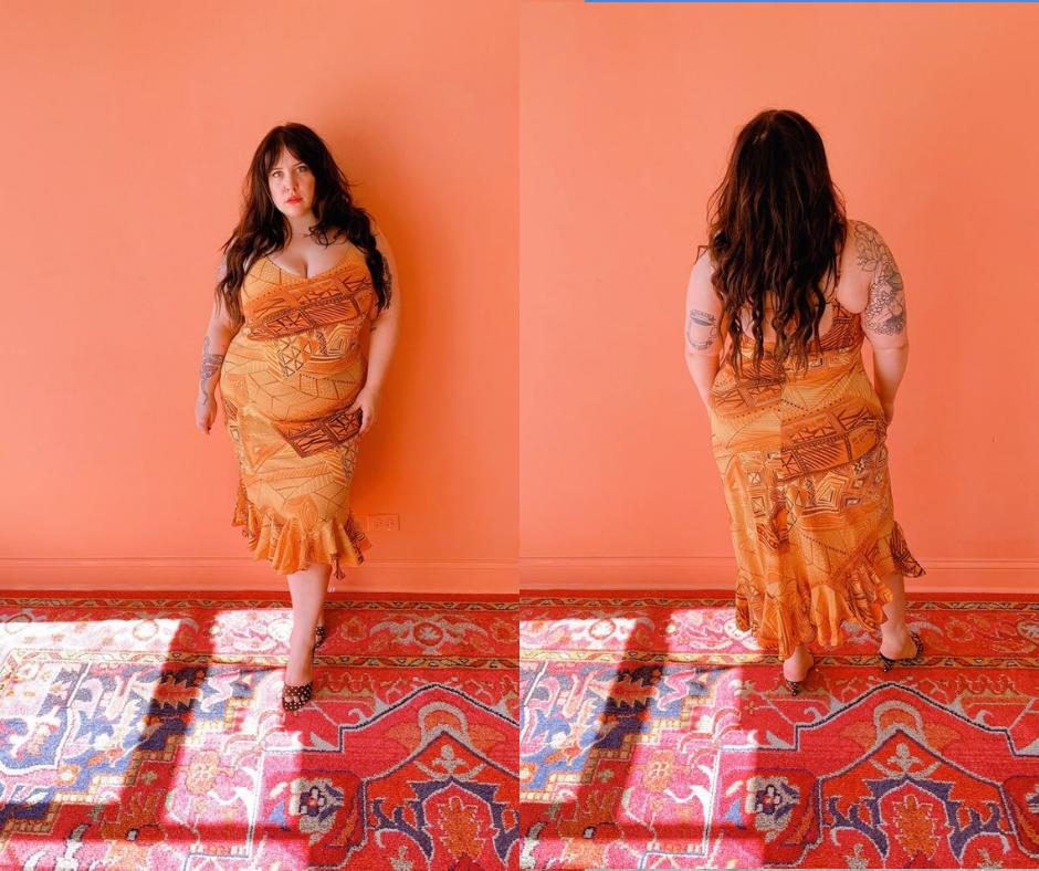 Plus size woman with long hair wearing a peach plus size vintage dress