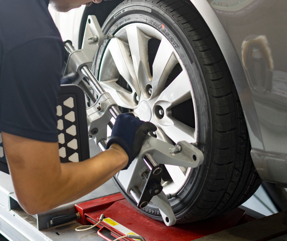 Mechanic putting a sensor on to a wheel prior to it getting a wheel alignment